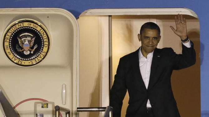 President Barack Obama waves as he walks down the stairs of Air Force One upon his arrival at Palm Beach International Airport, Friday, Feb. 15, 2013 in West Palm Beach, Fla. (AP Photo/Wilfredo Lee)