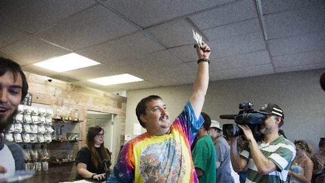 CORRECTS NAME TO BOYER, INSTEAD OF BOYD - Mike Boyer turns to the crowd outside, showing off the 4 grams of marijuana he bought as the first in line to legally purchase marijuana at Spokane Green Leaf, Tuesday, July 8, 2014, in Spokane, Wash. Twenty months after voters legalized recreational cannabis for adults over 21, Washington state's first few licensed pot shops opened for business Tuesday, catering to hundreds of customers who lined up outside, thrilled to be part of the historic moment. (AP Photo/The Spokesman-Review, Dan Pelle)
