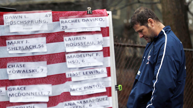 A man pays respects near a U.S. flag donning the names of victims on a makeshift memorial in the Sandy Hook village of Newtown, Conn., as the town mourns victims killed in a school shooting, Monday, Dec. 17, 2012. Authorities say a gunman killed his mother at their home and then opened fire inside the Sandy Hook Elementary School in Newtown, killing 26 people, including 20 children, before taking his own life, on Friday. (AP Photo/Julio Cortez)