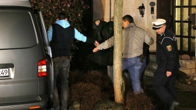 A person covered with a black blanket is led by police officers from the hours of the family of Andreas Lubitz to a police van in Montabaur, Germany, Thursday, March 26, 2015. Lubitz was the copilot on flight Germanwings 9525 that crashed with 150 people on board on Tuesday in the French Alps. (AP Photo/Michael Probst)