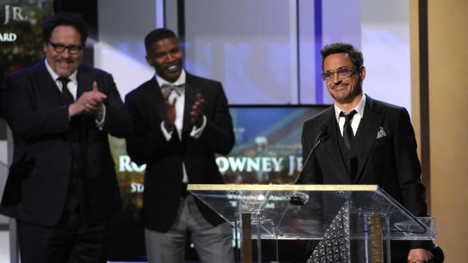 Robert Downey Jr. accepts the Stanley Kubrick award for excellence in film at the BAFTA Los Angeles Britannia Awards at the Beverly Hilton Hotel on Thursday, Oct. 30, 2014, in Beverly Hills, Calif. Looking on from left are presenters Jon Favreau and Jamie Foxx. (Photo by Chris Pizzello/Invision/AP)
