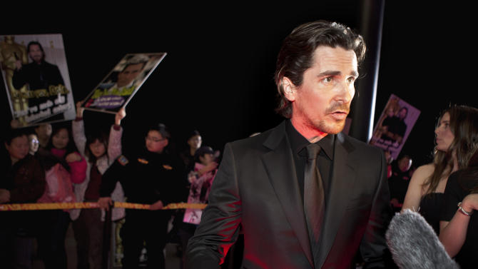 """FILE - In this file photo taken Monday, Dec. 12, 2011, English actor Christian Bale speaks to journalists during an interview on the red carpet as he arrives for an event of the Zhang Yimou-directed new movie """"The Flowers of War"""" in Beijing, China. Academy Award winner Bale, in the midst of promoting the film he made in China that some critics have called propaganda, has been stopped trying to visit a blind activist living under house arrest, with a CNN camera crew in tow. CNN posted footage of a scuffle between Bale and the activist's guards on its website Friday, Dec. 16. (AP Photo/Andy Wong, File)"""