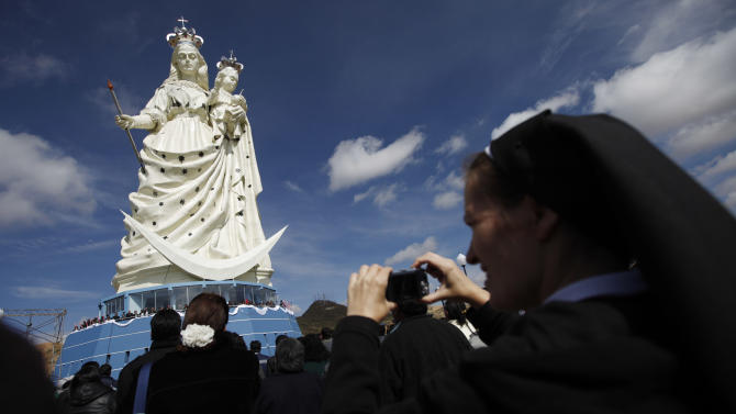 """A nun takes pictures of a newly unveiled statue of the Virgin Mary holding a baby Jesus on Santa Barbara hill in the mining city of Oruro, Bolivia, Friday, Feb. 1, 2013. The 45 meter (147 feet) statue that took four years to build, known in Spanish as """"Virgen del Socavón,"""" or the Virgin of the Tunnel, is Oruro's patron, venerated in particular by miners and folkloric Carnival dancers. (AP Photo/Juan Karita)"""