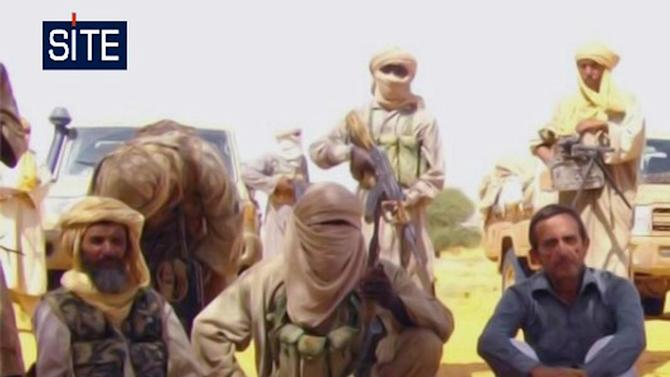 FILE - This image taken from video  and provided by U.S.-based SITE Intelligence Group Thursday Sept. 30, 2010 shows a foreign hostage  who was among seven seized in Niger by an al-Qaida offshoot, according to a group that monitors terrorism. In October 2010 French media reported that an earlier hostage of the group had identified the captor at left in the image as Abu Zeid,  a senior leader of Al-Qaida in the Islamic Maghreb. Chadian authorities on Friday March 1 2013 announced their forces had killed Abu Zeid in fighting in northern  Mali.   (AP Photo/SITE)  **  EDITORIAL USE ONLY  **