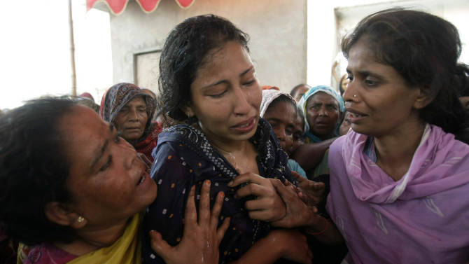 Women comfort a Pakistani wife who lost her husband, shot dead in Karachi, Pakistan on Friday, July, 8, 2011. Security forces were ordered to shoot gunmen on sight Friday in Pakistan's largest city, after three days of violence that killed scores of people and prompted political leaders to call for a day of mourning that shut businesses and kept public traffic off the roads. This week's violent spate in Karachi was among the worst this year for a city that has long been a hotbed of ethnic, sectarian and political tensions.  (AP Photo/Fareed Khan)