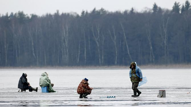 Fishermen catch the fish on the ice of a lake despite the warmer weather near the village of Babiy Les
