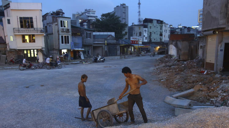 In this photo taken on May 12, 2012, two workers move materials to a cart near Cat linh street, the starting point of the Hanoi Urban Railways: Cat Linh-Ha Dong Route Project, which is delayed due to the late in land clearance for construction. Planners warn that if Hanoi doesn't build more roads and efficient public transport while limiting car ownership, its narrow streets will begin to look as gridlocked as those of Jakarta and other notoriously congested megacities. (AP Photo/Na Son Nguyen)