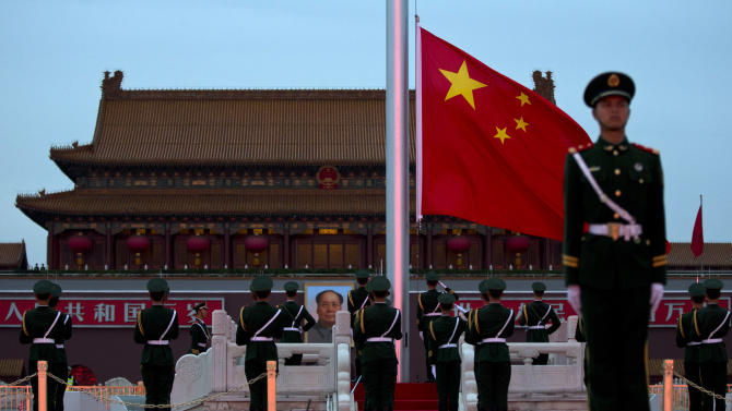 Paramilitary policemen stand at attention and salute while the Chinese national flag is lowered at sunset Wednesday, Nov. 7, 2012, on Tiananmen Square, near the Great Hall of the People, where the Chinese Communist Party's 18th National Congress is scheduled to begin Thursday in Beijing. The once-a-decade event installs a new leadership to run the world's second largest economy and newly assertive global power. (AP Photo/Alexander F. Yuan)