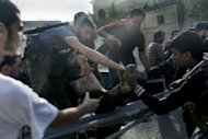 Syrian rebel fighters and locals help a man from a pick-up truck after he was wounded in shelling by government forces in Qusayr, southwest of Homs, in western Syria on Thursday