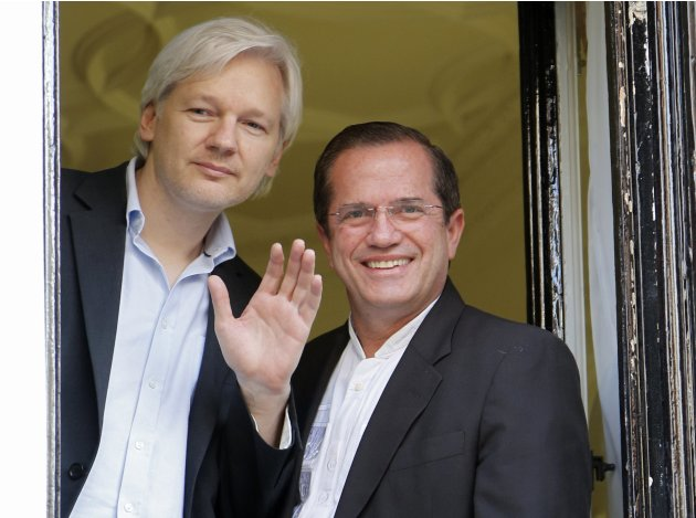 WikiLeaks founder Julian Assange waves from a window with Ecuador's Foreign Affairs Minister Ricardo Patino at Ecuador's embassy in central London