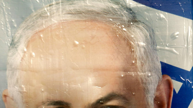 A vandalized election campaign billboard of Israeli Prime Minister and Likud Party leader Benjamin Netanyahu hangs on a main road in Tel Aviv, Israel, Monday, Jan. 21, 2013.  The general elections will be held on Tuesday, Jan. 22, 2013. (AP Photo/Ariel Schalit)