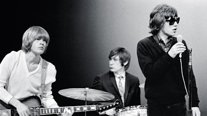 """This Nov. 11, 1965 photo supplied by the Rock and Roll Hall of Fame and Museum shows, from left, Brian Jones, Charlie Watts and Mick Jagger of The Rolling Stones on the NBC teen music show """"Hullabaloo,"""" in New York. Rare photos of the young Rolling Stones, taken by their tour manager Bob Bonis during their first years in the United States, will be unveiled during the Rock and Roll Hall of Fame's celebration of the group next month. The photos will be shown as part of a weeklong tribute to the band for the Rock Hall's Music Masters Series, from Oct. 21 to Oct. 26. (AP Photo/Rock and Roll Hall of Fame and Museum, Bob Bonis)"""