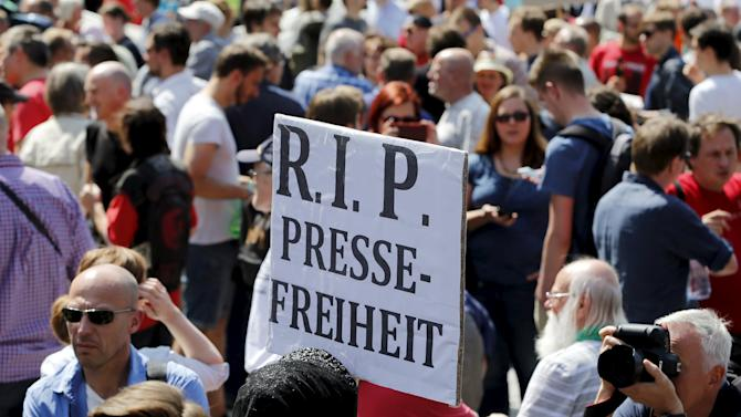A demonstrator holds up a placard during a rally to protest against a criminal complaint by the domestic intelligence agency, the Office for the Protection of the Constitution, in Berlin