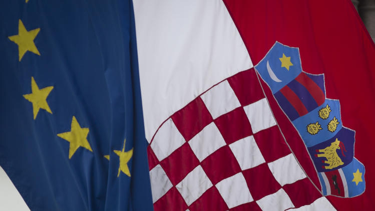 A Croatian, right, and a EU flag fly in downtown in Zagreb, Croatia, Sunday, June 30, 2013. Croatia is to join the European Union on July 1, 2013. (AP Photo/Darko Bandic)