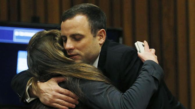 Oscar Pistorius is greeted by a well-wisher at a court in Pretoria, South Africa, Tuesday, July 1, 2014. The murder trial of Pistorius resumed Monday, June 30, after one month during which mental health experts evaluated the athlete to determine if he has an anxiety disorder that could have influenced his actions on the night he killed girlfriend Reeva Steenkamp. (AP Photo/Mike Hutchings, Pool)