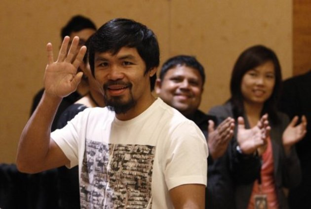 Boxer Manny Pacquiao of the Philippines waves as he arrives for a news conference in Singapore August 2, 2013. Pacquiao will fight Brandon Rios of the U.S. in a welterweight bout at the Venetian Macao in Macau on November 24. (REUTERS PHOTO / Edgar Su)