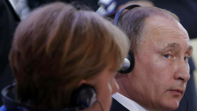 Russian President Putin talks to German Chancellor Merkel during the opening session of the World Climate Change Conference 2015 (COP21) at Le Bourget, near Paris