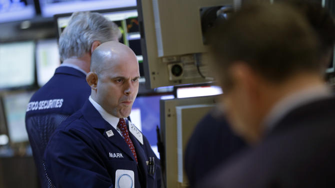 Traders work on the floor at the New York Stock Exchange in New York, Monday, April 22, 2013.  Stocks edged lower on Wall Street at the start of a big week for company earnings. About a third of the companies in the S&P 500, including Exxon Mobil and Apple, are reporting earnings this week. Analysts currently expect earnings to rise by 2 percent in the first quarter, down from the 7.7 percent increase in the fourth quarter, according to S&P Capital IQ. (AP Photo/Seth Wenig)