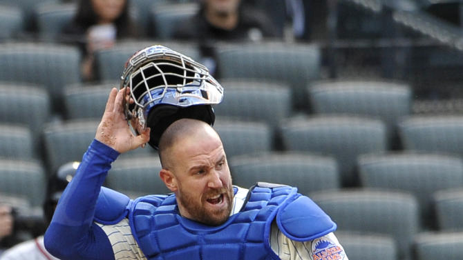 New York Mets catcher John Buck reacts to the safe call of Atlanta Braves' Jordan Schafer at home plate in the tenth inning of a baseball game that was suspended from Friday night at Citi Field, Saturday, May 25, 2013 in New York. The Braves won 7-5. (AP Photo/Kathy Kmonicek)