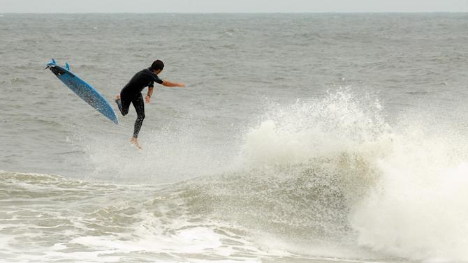 A surfer enjoys the waves generated by Hurricane Sandy Friday Oct 26, 2012 along Pleasure Island, N.C. The region will see sustained winds of about 30 to 40 mph on Saturday evening that will continue into Sunday, according to the National Weather Service Wilmington station. Winds will be highest along the coast. (AP Photo/The Star-News, Ken Blevins)