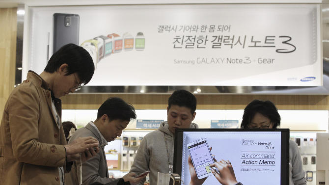 Visitors try out Samsung Electronics Co.'s Galaxy Note 3 at its showroom in Seoul, South Korea, Tuesday, April 1, 2014. Declining smartphone prices hit profit at Samsung for a second straight quarter. The consumer technology heavyweight said Tuesday that it expects operating income of about 8.4 trillion won ($8 billion) for the January-March quarter, down 4 percent from a year earlier. (AP Photo/Ahn Young-joon)