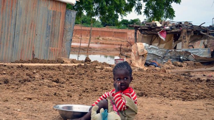 A child sits near the ruins of his parents' home on September 5, 2013 in a district in Niamey