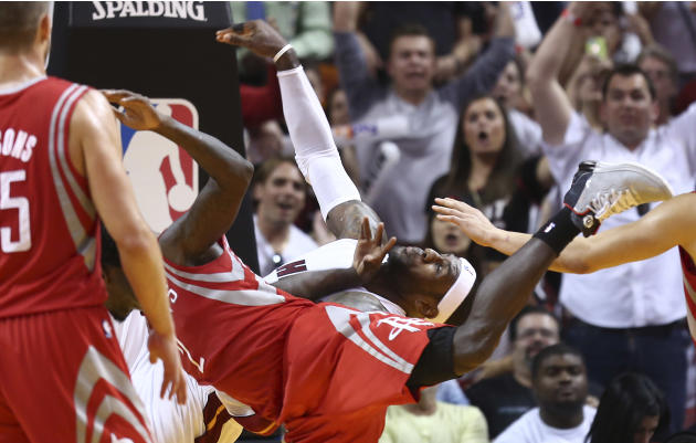 After blocking Miami Heat's LeBron James, back, Houston Rockets' Patrick Beverley (2) falls to the court floor during the second half of an NBA  basketball game in Miami, Sunday, March 16, 201
