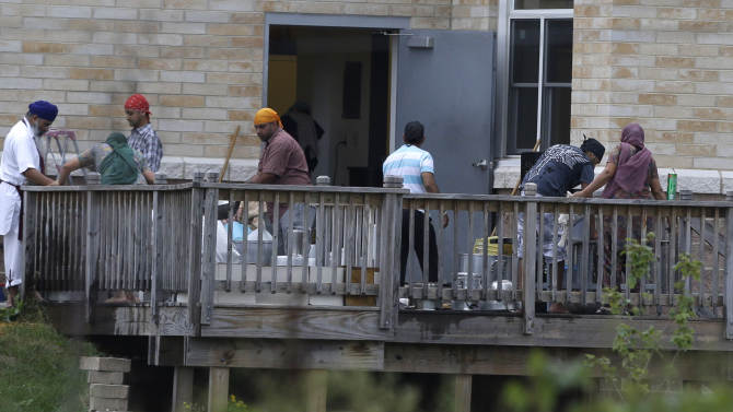 Members of the Sikh temple of Wisconsin wash items as they return for the first time in Oak Creek, Wis., Thursday, Aug 9, 2012.  The mass shooting last Sunday claimed six members of the temple. (AP Photo/Jeffrey Phelps)