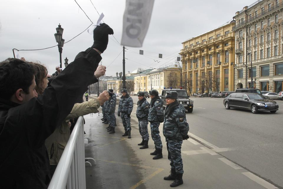 Russian opposition members with white ribbons protest outside the parliament building as Russian Prime Minister Vladimir Putin's motorcade passes by, Moscow, Wednesday, April 11, 2012. Russia's prime minister Vladimir Putin is to speak at Parliament on Wednesday in his first major public speech since his victory at the March 4 presidential election. (AP Photo/Misha Japaridze)