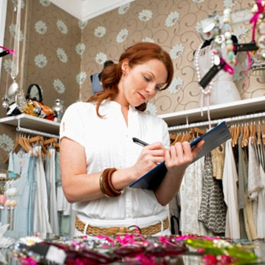 Young-woman-in-clothes-shop-holding-clipboard-and-writing_web