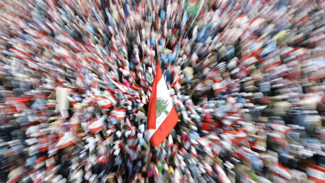 Lebanese people carry national flags as they attend a rally in Beirut's Martyrs' Square, Lebanon, Sunday, March. 13, 2011. Thousands of flag-waving Lebanese gathered in Beirut's main square Sunday to mark the sixth anniversary of the assassination of former Prime Minister Rafik Hariri, a killing that sparked a cascade of political turmoil in the Middle East. (AP Photo / Bilal Hussein)