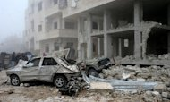 A handout picture released by the Syrian Arab News Agency (SANA) shows Syrians inspecting the site of a suicide car bombing in Salmiyeh, a town in the central province of Hama, on January 22, 2013