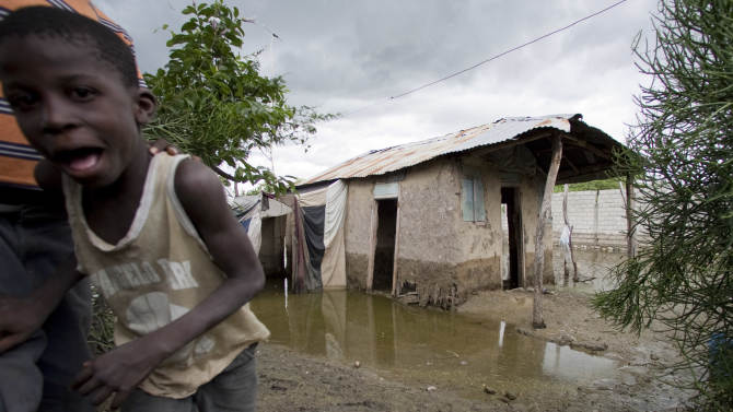 A boy looks at the camera as he walks past a partially flooded house on the outskirts of L'Estere, Haiti. Thursday, Aug. 4,  2011. Tropical Storm Emily broke apart Thursday and became a wet low pressure system after dumping rains over part of Haiti and the southwestern corner of the Dominican Republic, the U.S. National Hurricane Center said. (AP Photo/Dieu Nalio Chery)