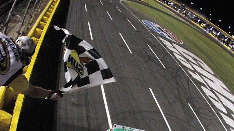 Kasey Kahne takes the checkered flag to win the NASCAR Coca-Cola 600 Sprint Cup Series auto race in Concord, N.C., Sunday, May 27, 2012. (AP Photo/HHP, Pool)  NO SALES