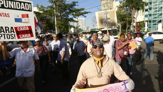 A man holds a placard as he takes part in an anti-corruption march and a protest against Ricardo Martinelli in Panama City