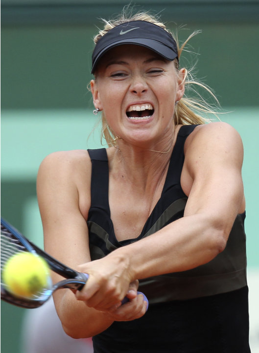 Russia's Maria Sharapova returns the ball to Japan's Ayumi Morita during their second round match in the French Open tennis tournament at the Roland Garros stadium in Paris, Friday, June 1, 2012.  Sha