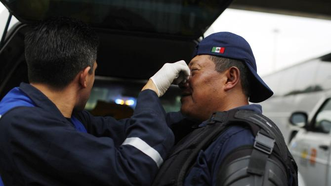 A paramedic tends to the injury of a riot policeman during clashes with masked demonstrators after a protest over the 43 missing Ayotzinapa students near the Benito Juarez International airport in Mexico City
