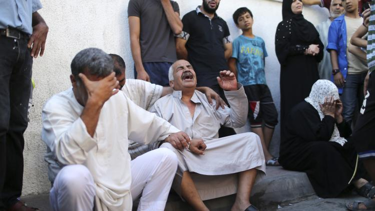 The grandfather of three Palestinian children from the Al-Rifi family cries outside a hospital morgue in Gaza City
