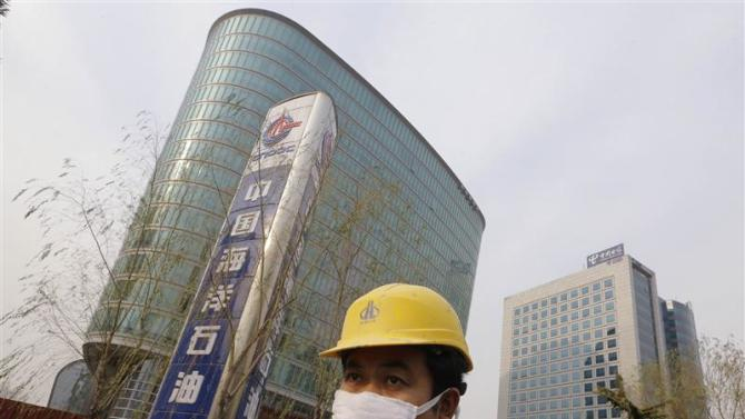 File photo of a worker standing near the headquarters building of China National Offshore Oil Corp (CNOOC) in Beijing