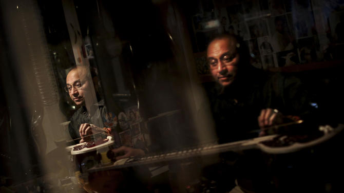 """Indian traditional instrument craftsman Sanjay Sharma places a fret on a sitar at his store Riki Ram's Music in New Delhi, India, Thursday, Dec. 13, 2012. For close to a 100 years Sharma's family has created musical instruments for legendary Indian musicians. But none more famous than sitar virtuoso Ravi Shankar who died Tuesday at age 92. Described as """"the godfather of world music"""" by Beatle George Harrison, Shankar introduced millions of Westerners to the sitar and the centuries-old traditions of Indian classical music. (AP Photo/Kevin Frayer)"""