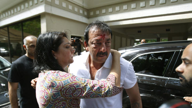 Priya Dutt tries to console her brother Indian Bollywood actor Sanjay Dutt, center,  after he broke down during a press conference at his residence in Mumbai, India, Thursday, March 28, 2013. Dutt said he has not sought pardon for a 1993 weapons conviction and will serve his prison sentence as ordered by India's Supreme Court. Dutt broke his silence a week after the court sentenced him to five years in prison for illegal possession of weapons supplied by Mumbai crime bosses linked to a 1993 terror attack that killed 257 people.(AP Photo/Rafiq Maqbool)