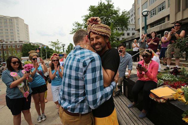 Todd Kinsman, 28, left, and Ravi Manghnani, 37, hug after getting married outside the City-County Building the day after the ban on same-sex marriage was struck down in Wisconsin, in Madison, Wis., Saturday, June 7, 2014. (AP Photo/Wisconsin State Journal, Amber Arnold)