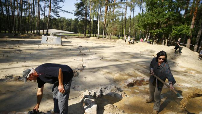 Archeologist Mazurek takes pictures as archelologist and historian Zalewska digs inside the perimeter of a Nazi death camp in Sobibor