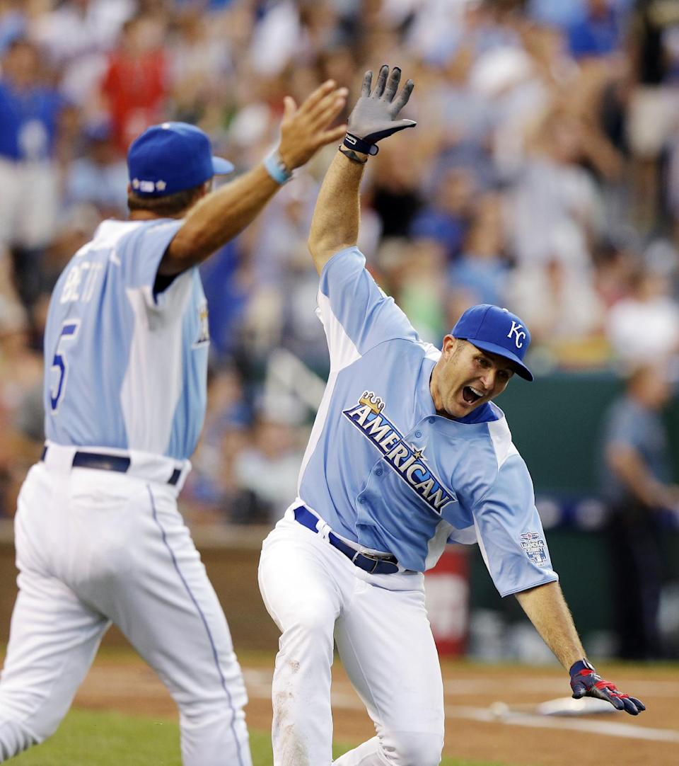 Mike Sweeney, right, former baseball player and current television analyst, and Hall of Famer George Brett celebrate after Sweeney hit a home run during the MLB All-Star celebrity softball game, Sunday, July 8, 2012, in Kansas City, Mo. (AP Photo/Charlie Riedel)