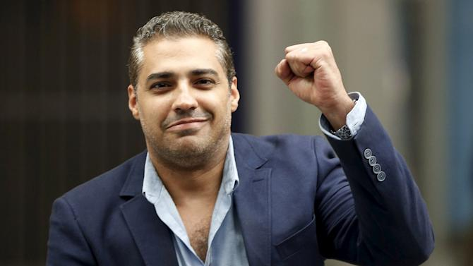 Canadian journalist Mohamed Fahmy, who was recently freed from jail in Egypt, gestures after arriving on a flight from Cairo, at London's Heathrow airport, Britain