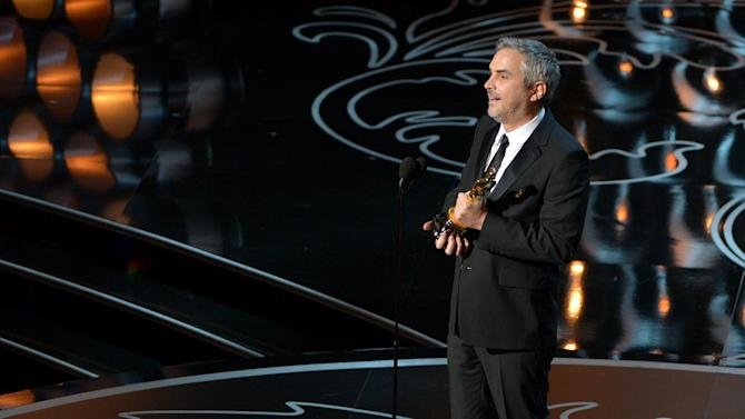 """Alfonso Cuaron accepts the award for best director of the year for """"Gravity"""" during the Oscars at the Dolby Theatre on Sunday, March 2, 2014, in Los Angeles. (Photo by John Shearer/Invision/AP)"""