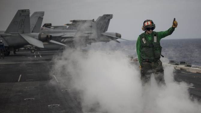 Handout photo shows Aviation Boatswain's Mate 2nd Class Tyler Stives inspecting a catapult after an aircraft launch aboard the aircraft carrier USS George Washington during Annual Exercise 2013, at sea