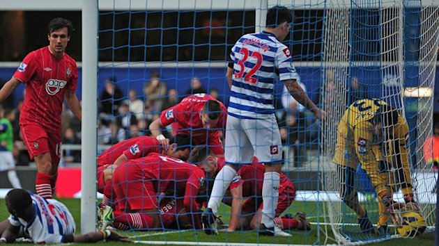 Queens Park Rangers' Brazilian goalkeeper Julio Cesar (R) fetches the ball from the back of the goal as Southampton players celebrate with Rickie Lambert after he scores the opening goal of the English Premier League football match