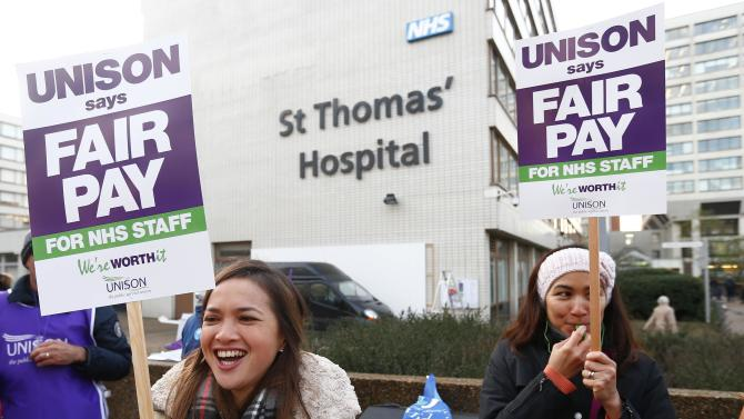 NHS workers hold placards as they stand on a picket line outside St. Thomas' Hospital in central London