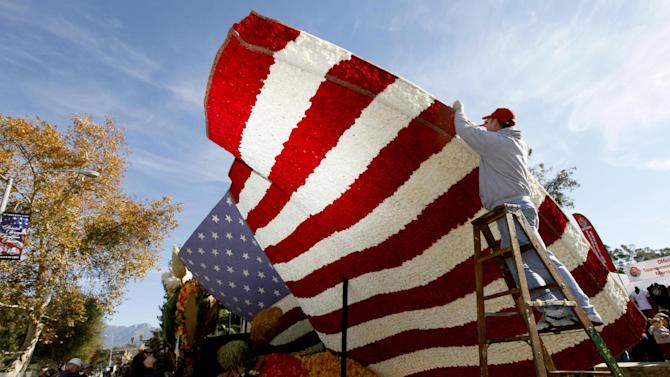 Volunteer David Burney from Milwaukee  helps put the finishing touches on the RDF TV rose float in Pasadena Monday, Dec. 31, 2012. (AP Photo/Nick Ut)